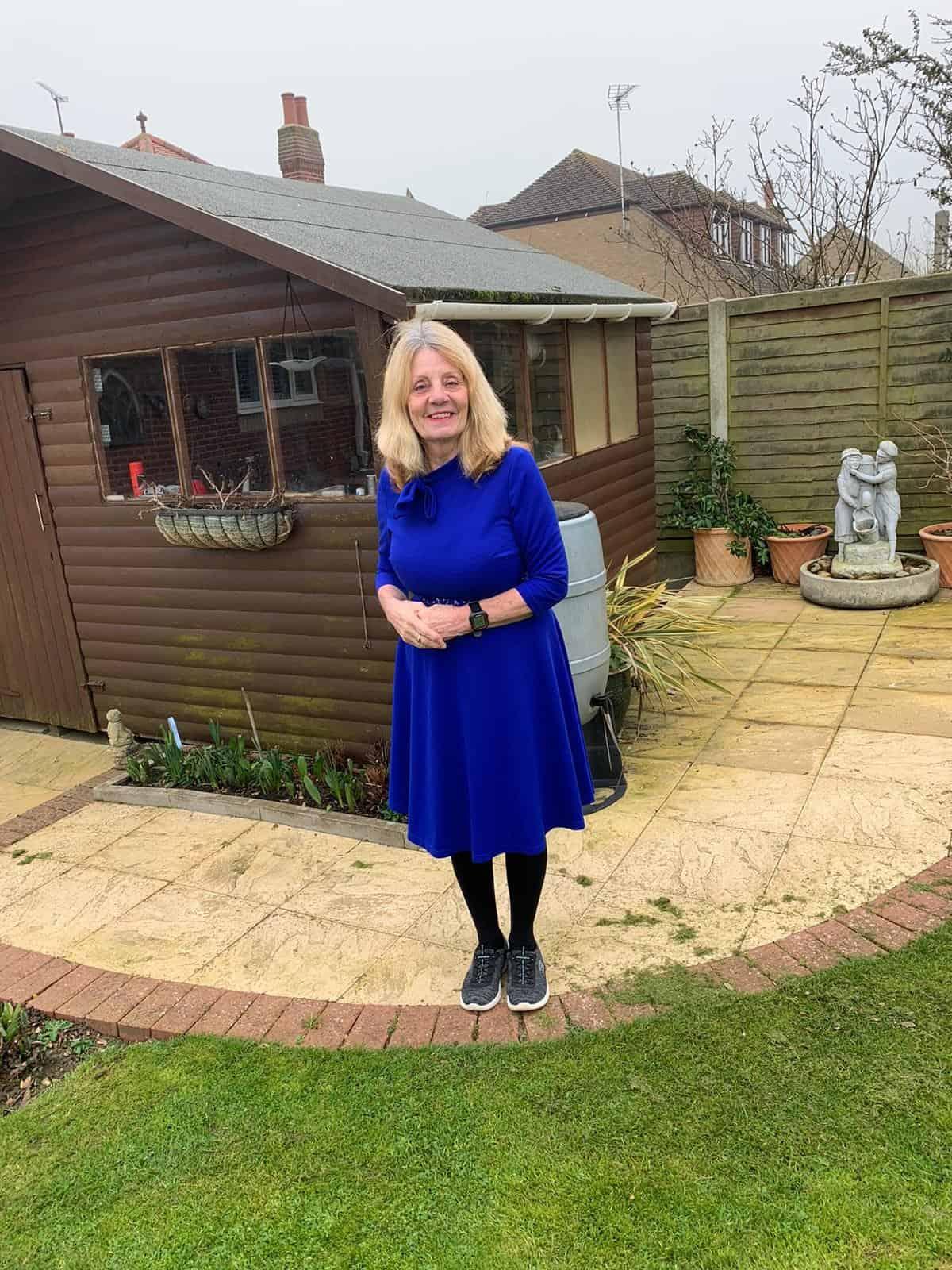 Linda standing in her garden