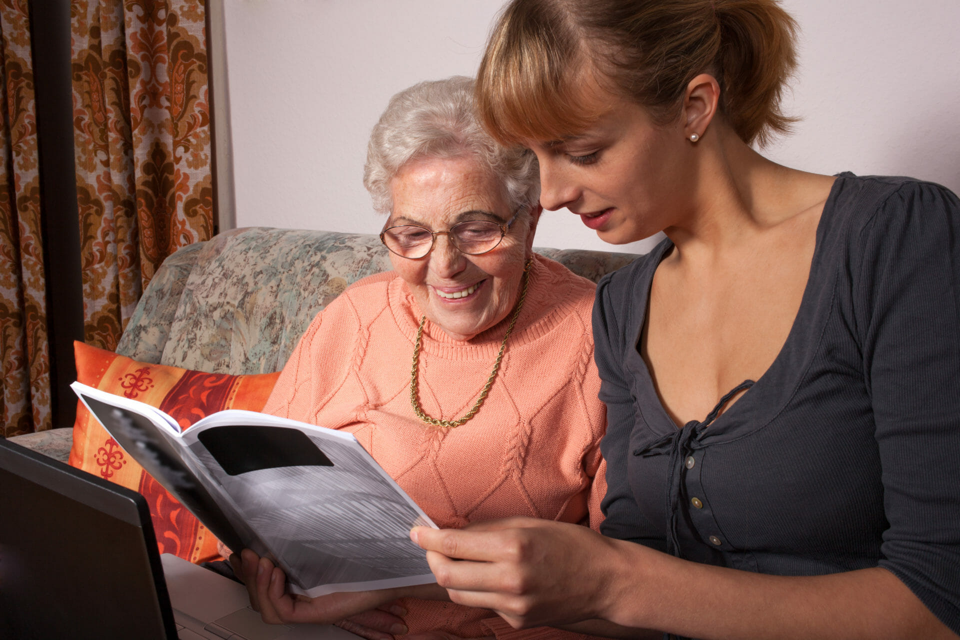 elderly lady sitting next to young woman looking at a magazine