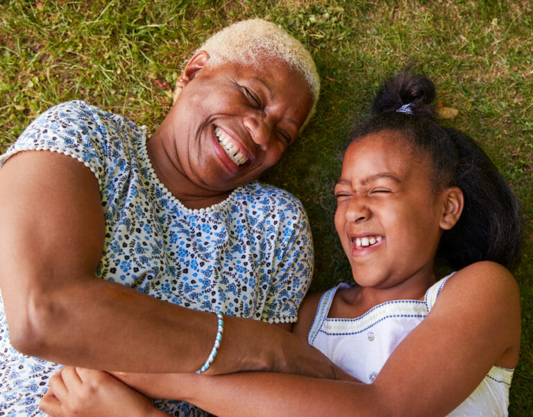 grandmother and granddaughter lying on ground laughing