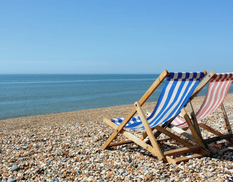 Deckchairs on beach in sun looking out onto sea