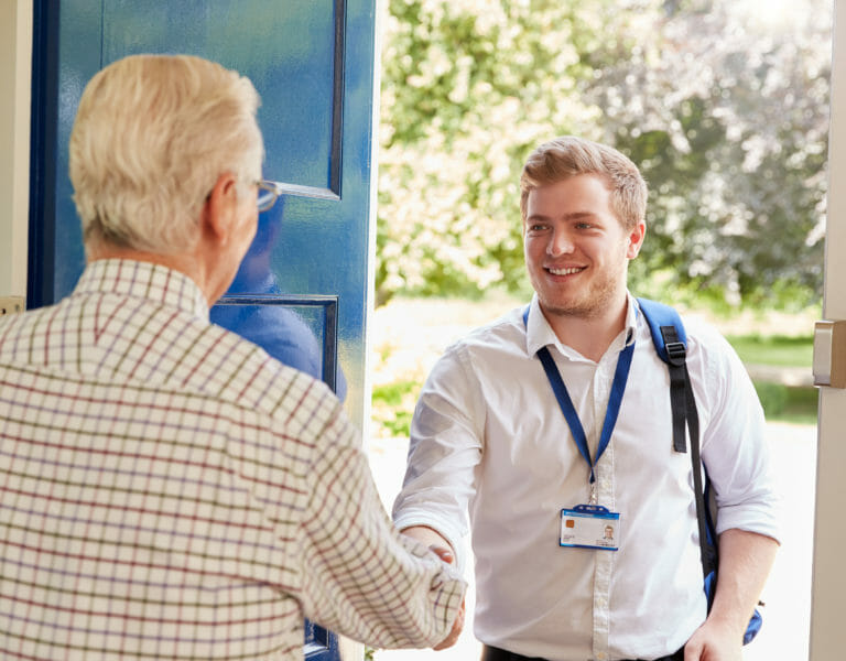 A support worker being greeted at the door