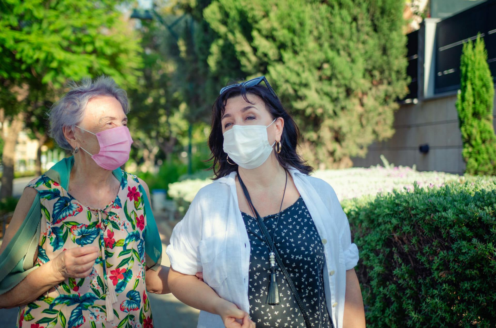 two women walking outside wearing masks