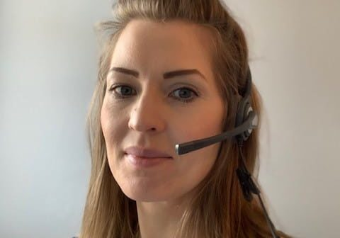 A woman with blond hair wearing a telephone headset and looking at the camera