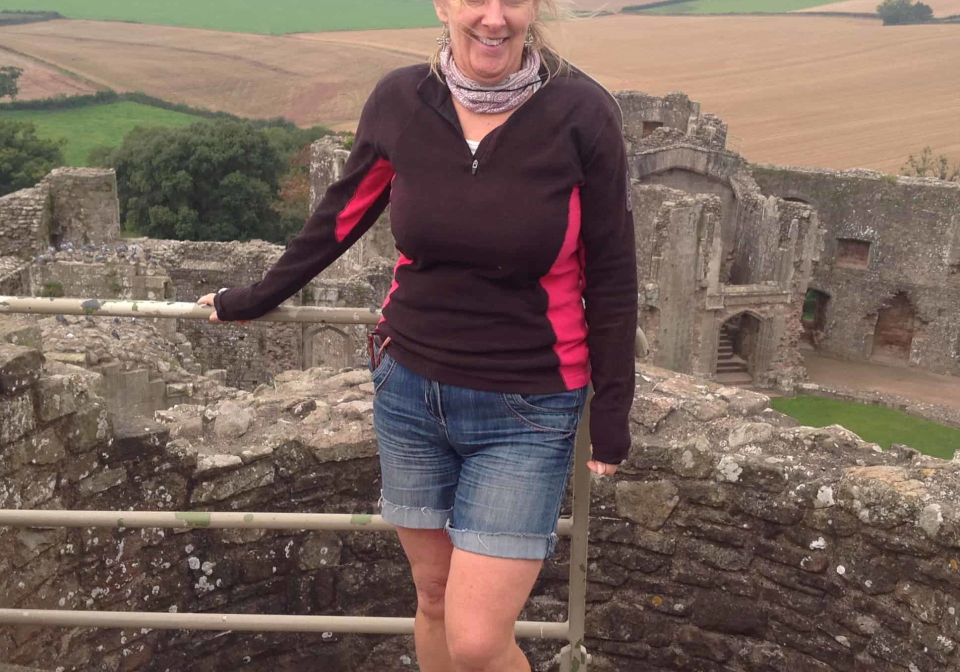 Karen standing in front of a stone wall overlooking countryside