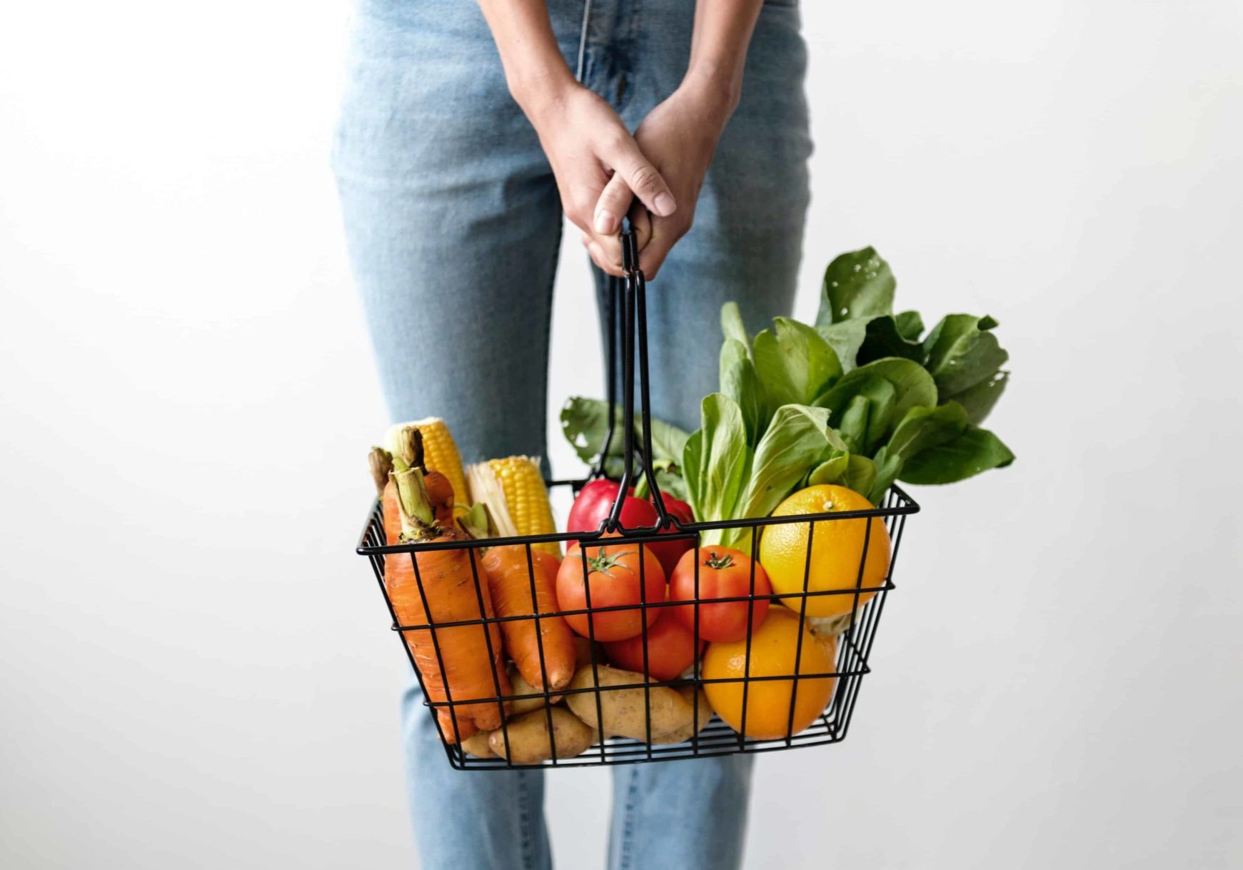 Person holding a basket full of vegetables
