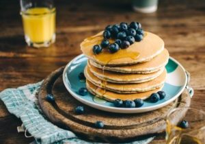 A stack of pancakes and a glass of orange juice