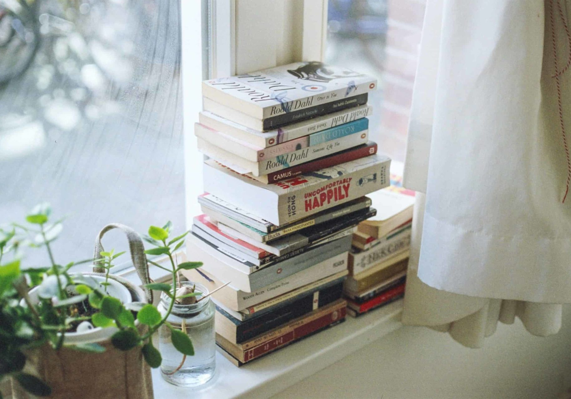 a pile of books on a window sill