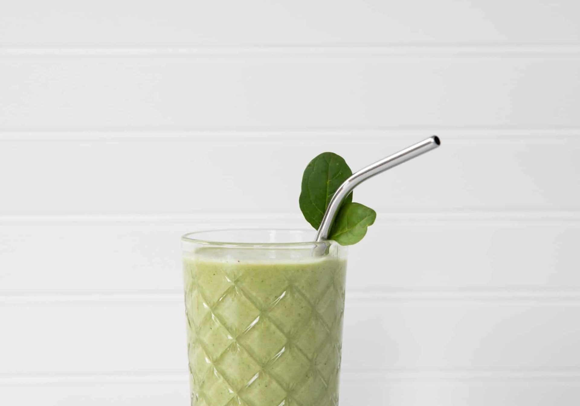 A green drink in a glass, with a metal straw and leaf garnish