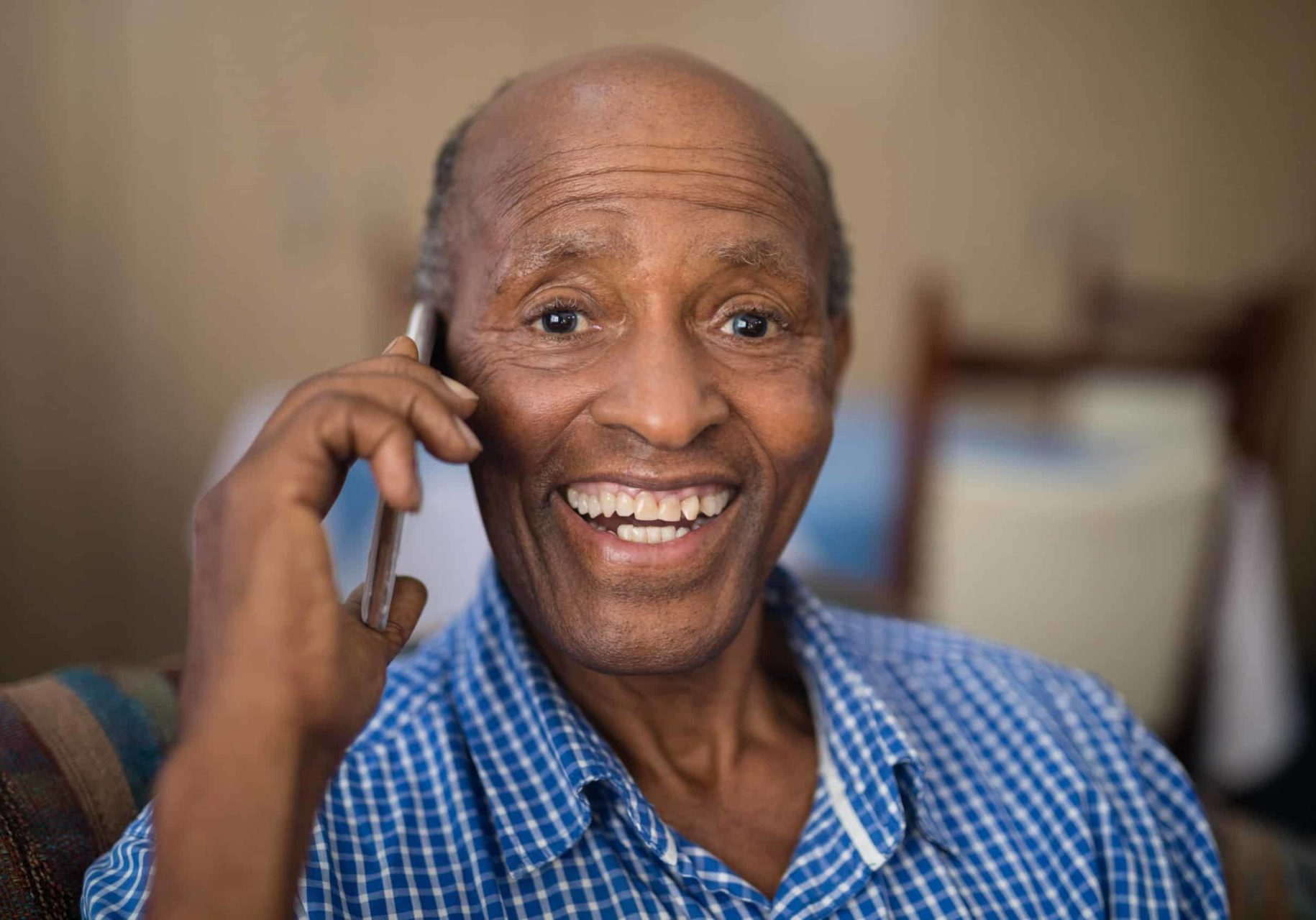 a man smiling and talking on the phone